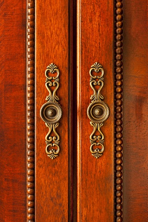 Ornate handles on wooden cabinet doors closeup photo