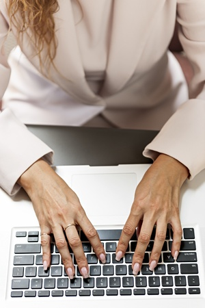 office use: Female hands typing on laptop keyboard from above