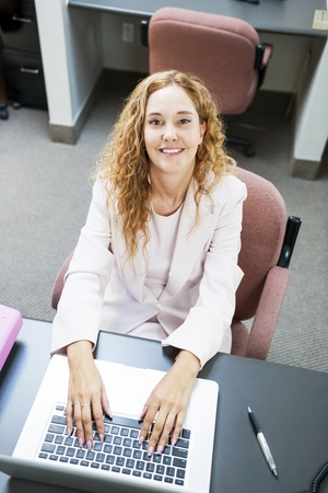 Smiling businesswoman sitting at workstation in office with computer photo