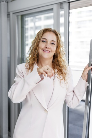 Smiling female real estate agent holding house keys in office photo