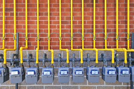 Row of natural gas meters with yellow pipes on building brick wall photo