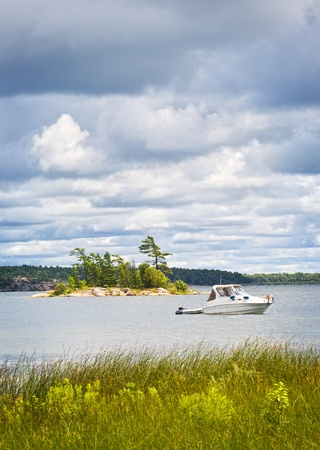 pleasure boat: Motorboat anchored with dinghy on lake in Georgian Bay, Ontario, Canada