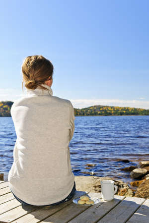 Woman sitting on dock relaxing by beautiful lake in Algonquin Park, Canada. Stock Photo