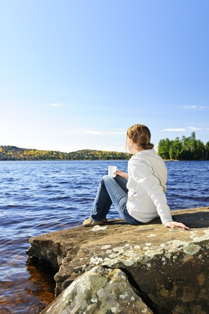 contemplative: Woman relaxing by beautiful lake on sunny fall day in Algonquin Park, Canada Stock Photo