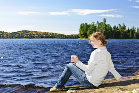 Young woman sitting with beverage on rock relaxing by beautiful lake in Algonquin Park, Canada. photo