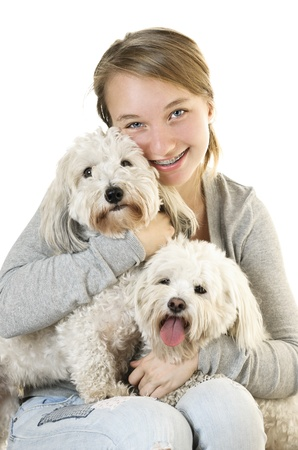Pretty teenage girl holding two adorable coton de tulear dogs photo