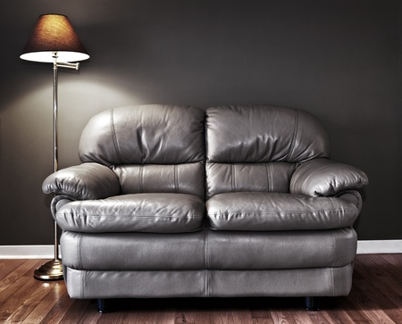 Leather love seat and floor lamp against dark wall photo