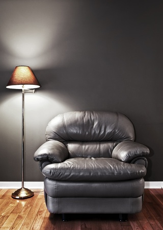 lighting fixtures: Leather chair and floor lamp against dark wall