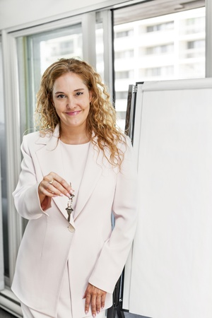 Smiling female real estate agent offering keys standing with blank flip chart photo