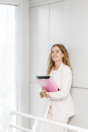 Confident career business woman standing in office hallway holding binder photo