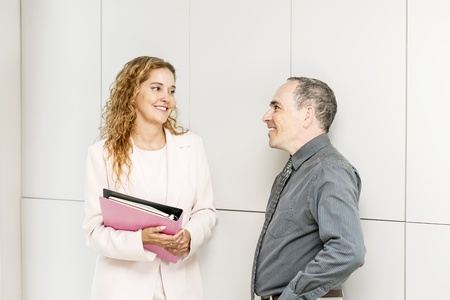 Man and woman discussing work in business office hallway photo