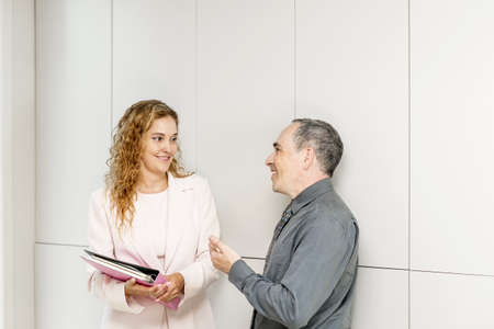 mentoring: Man and woman discussing work in business office hallway