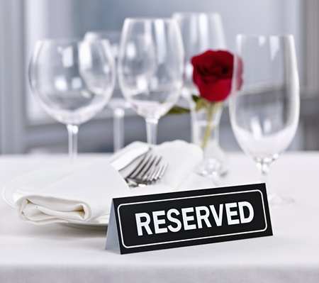 Reserved romantic restaurant table setting with roses plates and cutlery photo