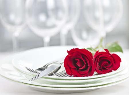 浪漫: 兩個浪漫的餐廳餐桌佈置與玫瑰盤子和餐具 版權商用圖片