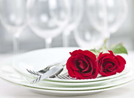 dinner: Romantic restaurant table setting for two with roses plates and cutlery