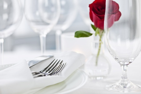 stemware: Romantic restaurant table setting with rose candle plates and cutlery Stock Photo