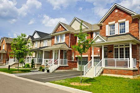 residential neighborhood: Suburban calle residencial, con una hilera de casas de ladrillo rojo