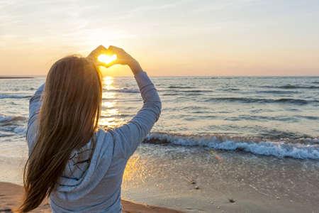 liefde: Blonde meisje bedrijf handen in hartvorm framing ondergaande zon bij zonsondergang op het strand oceaan