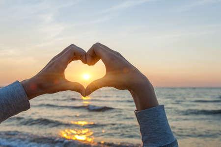 simbolo de paz: Las manos y los dedos en forma de marcos de sol del corazón en la puesta del sol sobre el océano