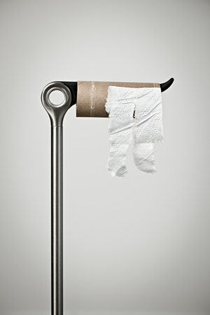 toilet: Metal stand with empty toilet paper roll Stock Photo