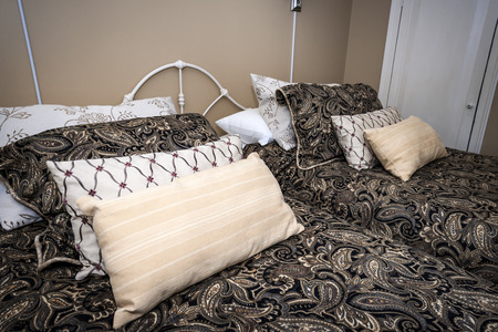 comforter: Two beds made with paisley bedspreads and pillows