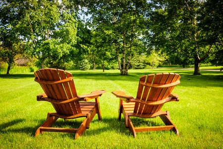 Zwei hölzerne Adirondack Stühle auf grünen Rasen mit Bäumen Standard-Bild