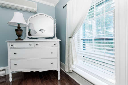 wood blinds: White painted dresser with mirror and lamp near window interior