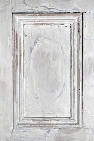 Old distressed wood door panel with peeling paint as framed background photo