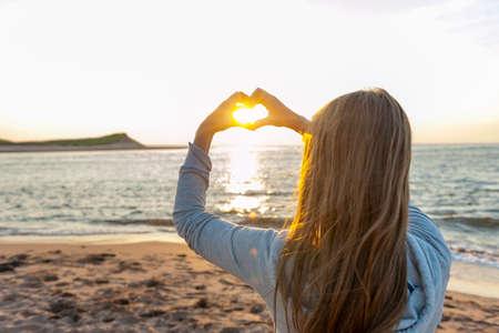 Blonde junge Mädchen mit Händen in Herzform Framing untergehende Sonne bei Sonnenuntergang am Meeresstrand