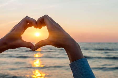 hacer el amor: Las manos y los dedos en forma de marcos de sol del corazón en la puesta del sol sobre el océano