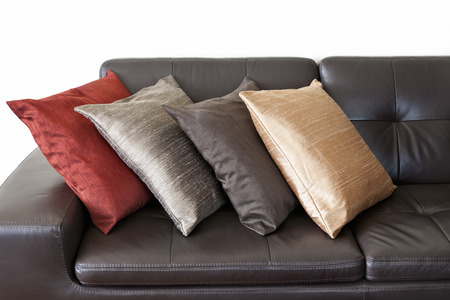 Four colorful cushions on dark brown leather couch Stock Photo - 22674640