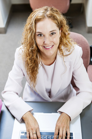 cubby: Smiling businesswoman sitting at workstation in office with computer Stock Photo