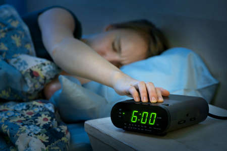 Young woman pressing snooze button on early morning digital alarm clock radio photo