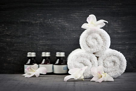 towels luxury: White rolled up towels with body care products at spa Stock Photo