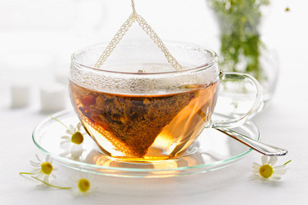 soothing: Glass teacup with soothing herbal tea in silk bag
