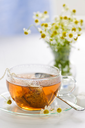 chamomile tea: Glass teacup with soothing herbal tea in silk bag