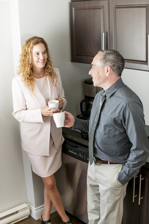 Man and woman having conversation in office coffee break area photo