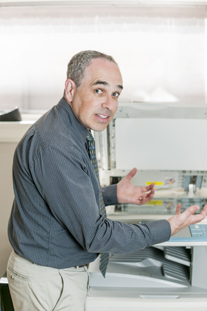 Business man having problem with photocopy machine in office looking frustrated and angry photo
