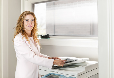 Smiling business woman operating photocopy machine in office photo