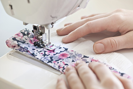 stitching machine: Closeup of hands guiding fabric through sewing machine needle and thread Stock Photo