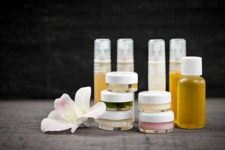 creams: Various jars and bottles of skin care products with orchid flower
