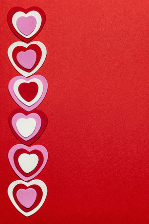 Border of romantic red pink and white hearts for Valentines day on crimson background