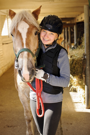 horse stable: Young female rider with horse inside stable
