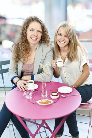 mujer tomando cafe: Dos mujeres sonrientes reunidos para tomar un café en la cafetería
