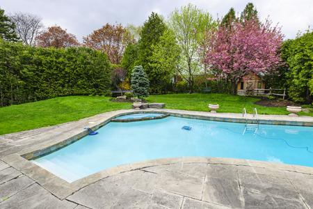 empedrado: Patio trasero con enterrada al aire libre privada residencial piscina y patio de piedra Foto de archivo