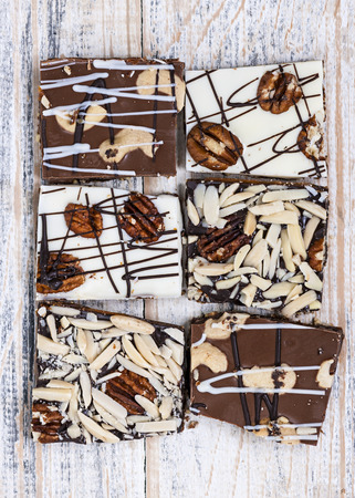 toffee: Assorted chocolate caramel bark pieces for sweet dessert arranged on wooden background, top view Stock Photo