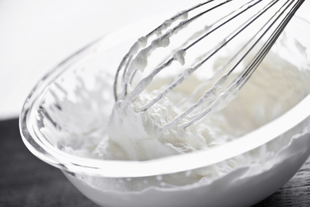 Closeup of metal whisk whipping cream in glass bowl photo
