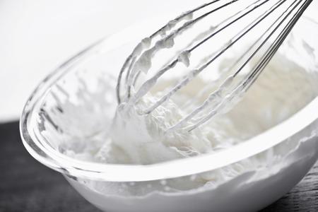 Nahaufnahme der Metall-Schneebesen Sahne in Glasschale