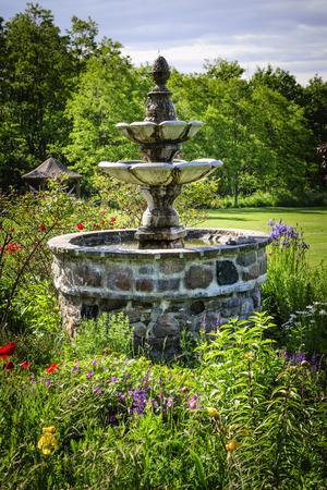 garden fountain: Lush green garden with tiered stone fountain Stock Photo