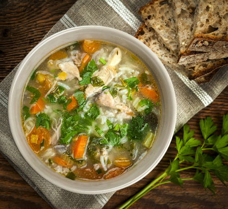 meaty: Chicken rice soup with vegetables in bowl and bread from above closeup Stock Photo